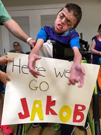 Jakob sits in a wheelchair with a handmade sign that reads Here We Go Jakob