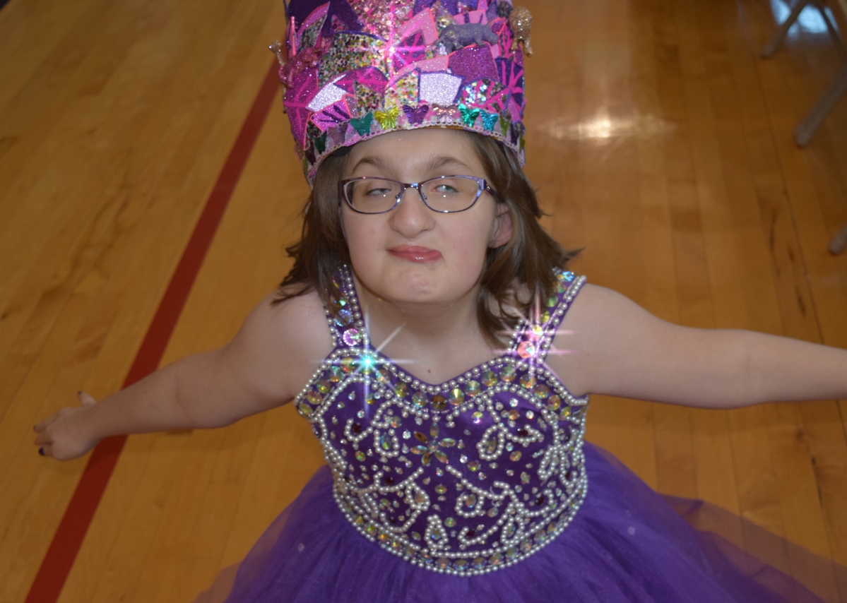 Laci with crown wearing a purple, jeweled dress.