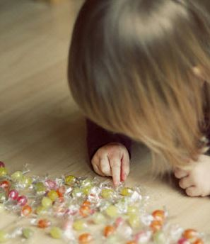 Young girl counting candies on hardwood floor.