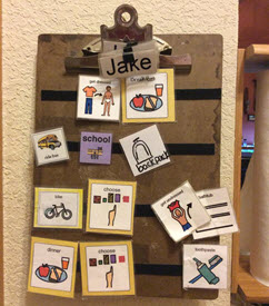 Clipboard with strips of Velcro to which picture symbols are attached
