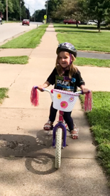 A young girl is on a sidewalk riding a bicycle that has a basket and pink streamers.