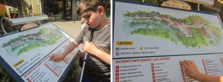 Liam reads Braille on a Disney Braille Map on a slanted board that has images, text, and braille.
