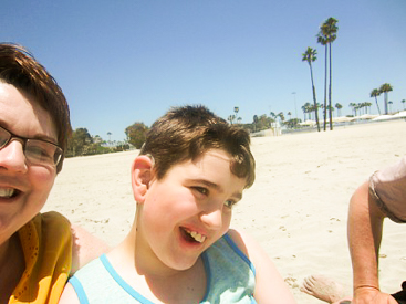 Liam and his mom are laughing on a sandy beach.