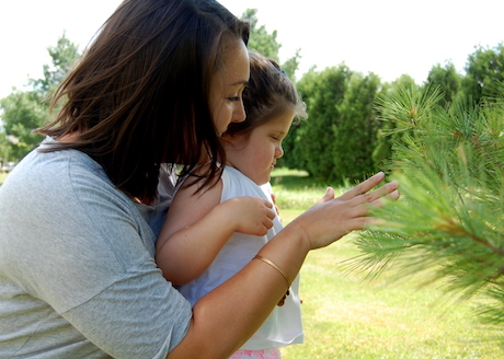 Young girl and intervener reach out to touch tree.