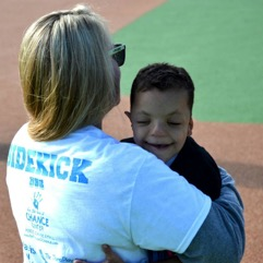 An adult hugs Devin, who is smiling