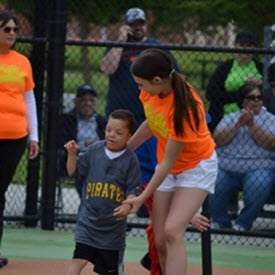 Devin runs with a partner on a baseball field