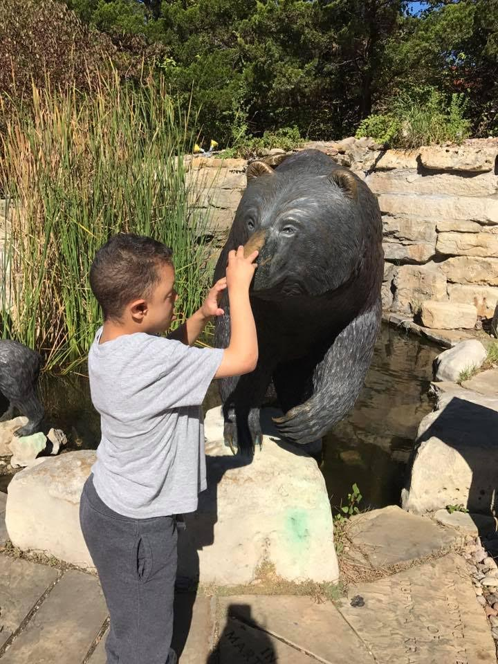 Devin reaches out to touch a bear statue.