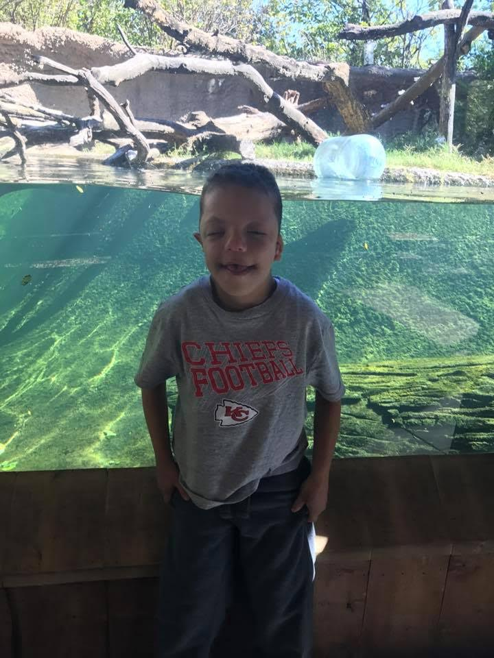 Devin stands in front of glass water tank where an animal lives at the zoo lives.
