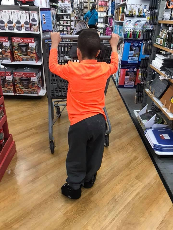 Devin pushing grocery cart in store.