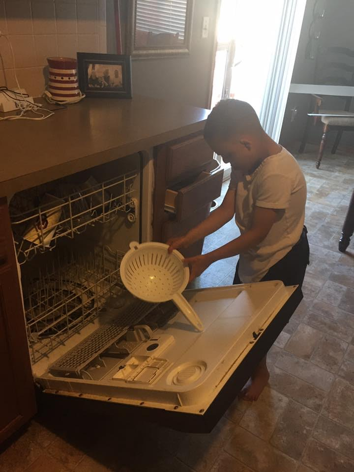 Devin puts a dish in the dishwasher.