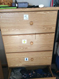 A dresser with a picture symbol on each drawer