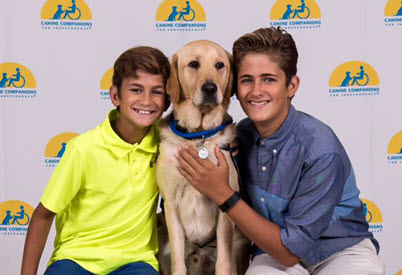 The boys pose with Erickson, a yellow lab