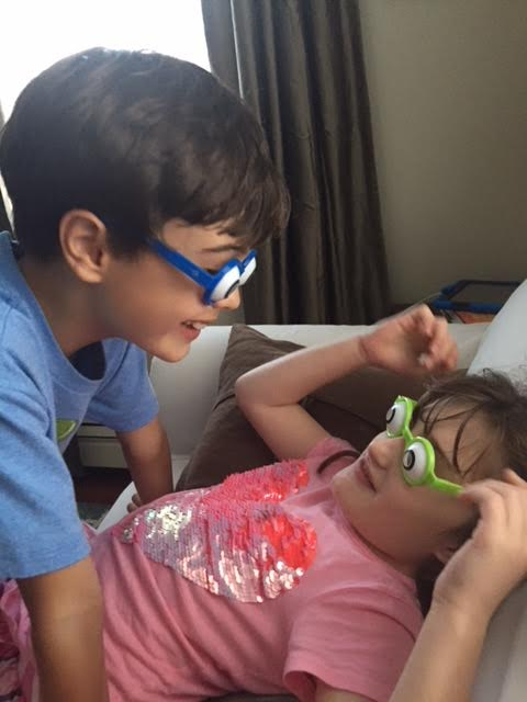 Two children wear big eye toy glasses.