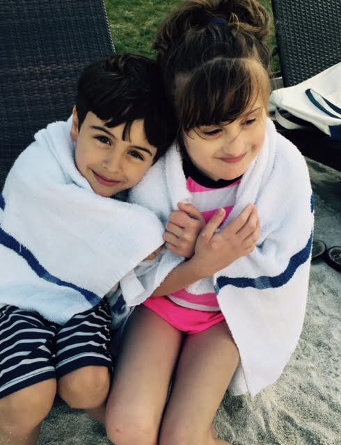 Grace and Jack sitting in sand with towel wrapped around each other.
