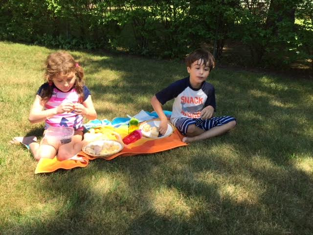 Grace and Jack sitting on a blanket having a picnic.