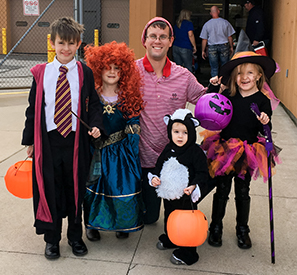 Teed family children (with their father) in Halloween costumes ranging from Harry Potter to an animal to a witch. They hold pumpkin baskets for candy. It's daylight and they are outside of a building.
