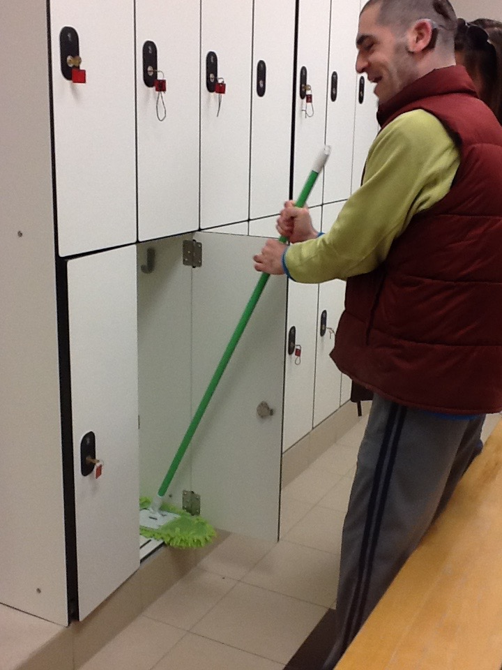 A young man using a broom to clean out lockers.