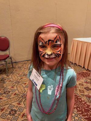 Young girl with lion face paint.
