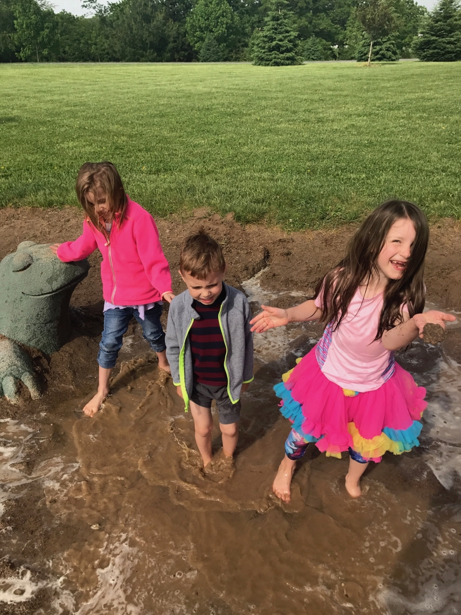 Two sisters and their brother jumping in a mud puddle.