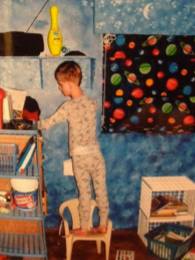 Jake as a young boy stands on a chair in his room and reaches for something