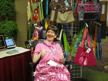 Jackie sits in front of a display of her bags
