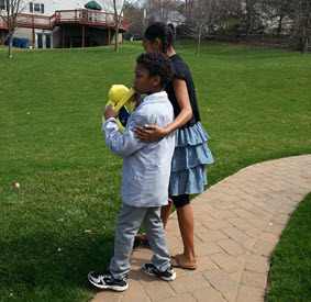 Jonathan hunts for eggs with his sister, who has her arm around him.