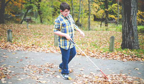 Liam walks with his cane on a road covered in fallen leaves