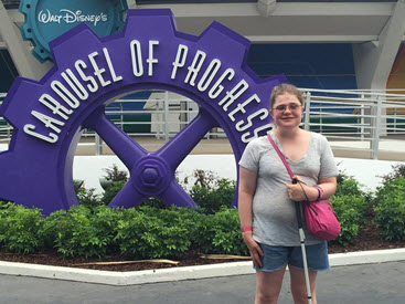 Megan, holding her cane, stands in front of the Carousel of Progress