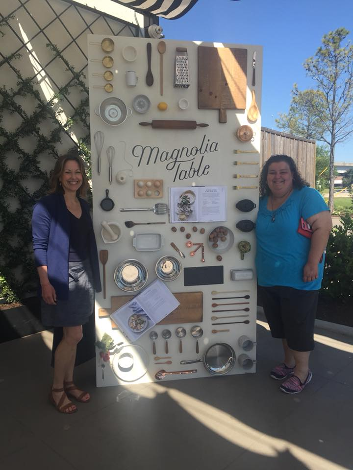 Minnie and Karin stand in front of a upright table titled Magnolia Table.