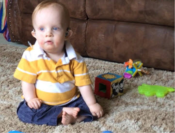 A toddler sits on the floor with some toys