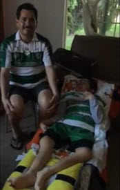 Norman and his father wear matching green and white striped jerseys