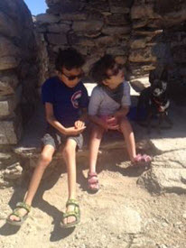 Soliz and Camila sit with their small dog on stone steps on a hike.