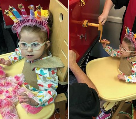 Mayzie at her birthday party wearing a birthday crown and turning a wheel to build a stuffed animal bear.