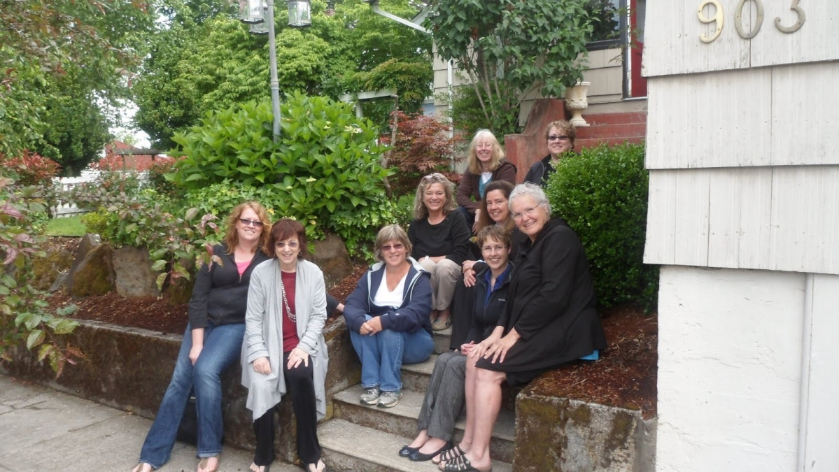 9 women sit on steps of house