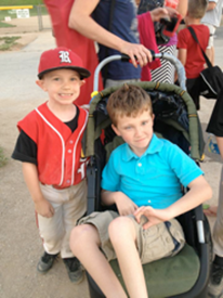 Ryan with his younger brother, who is dressed in baseball gear