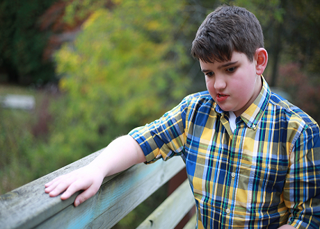 Young boy holding on to bridge handrail