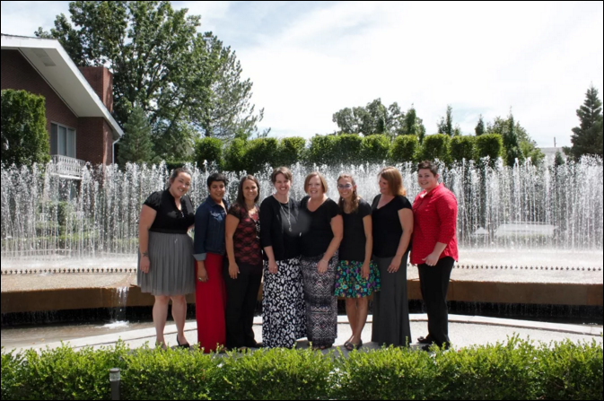 The eight women who served as intervener leaders are pictured standing in front of a fountain.