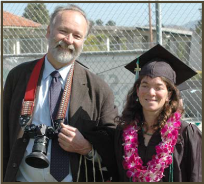 Woman in graduation cap and gown with man