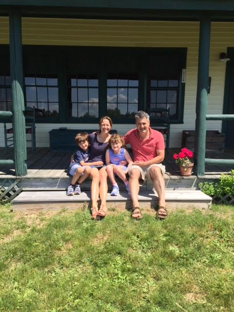 A family of four sit on a front porch.