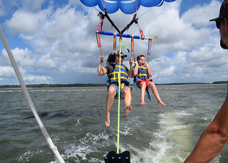 Mother and young daughter parasailing behind a boat