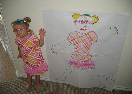 Lacy, a young girl, stands beside her self portrait