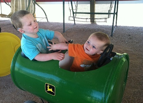 Two small boys riding in a toy car