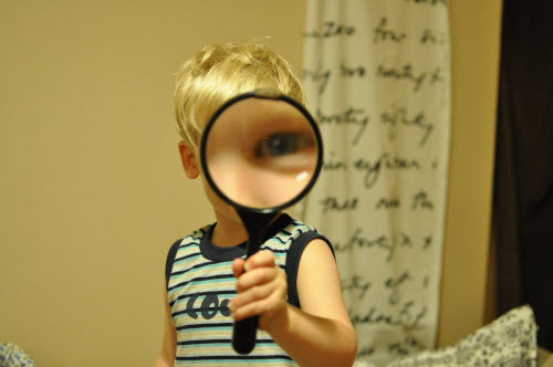 Young boy looking through large magnifying glass