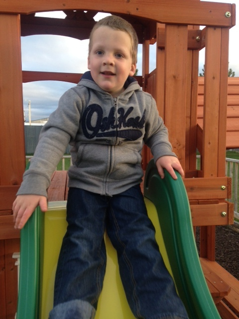 Liam sits at the top of a slide.