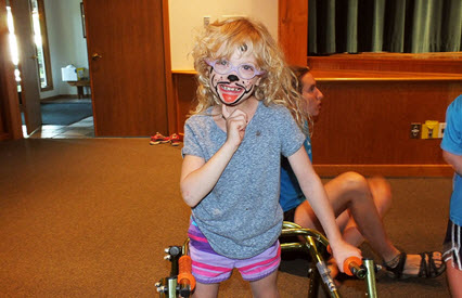 A young girl with her face painted stands in her walker, smiling