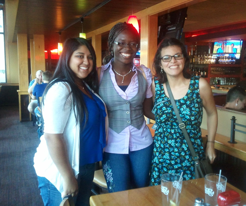 Christina takes a picture with some friends at a restaurant.