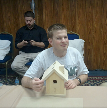 John takes a picture with a birdhouse that he has made.