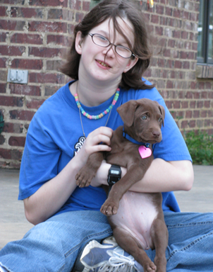 Aubre takes a picture with a chocolate lab puppy.