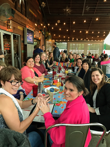 family engagement coordinators sitting at a long table an outdoor patio in Mexican food restaurant