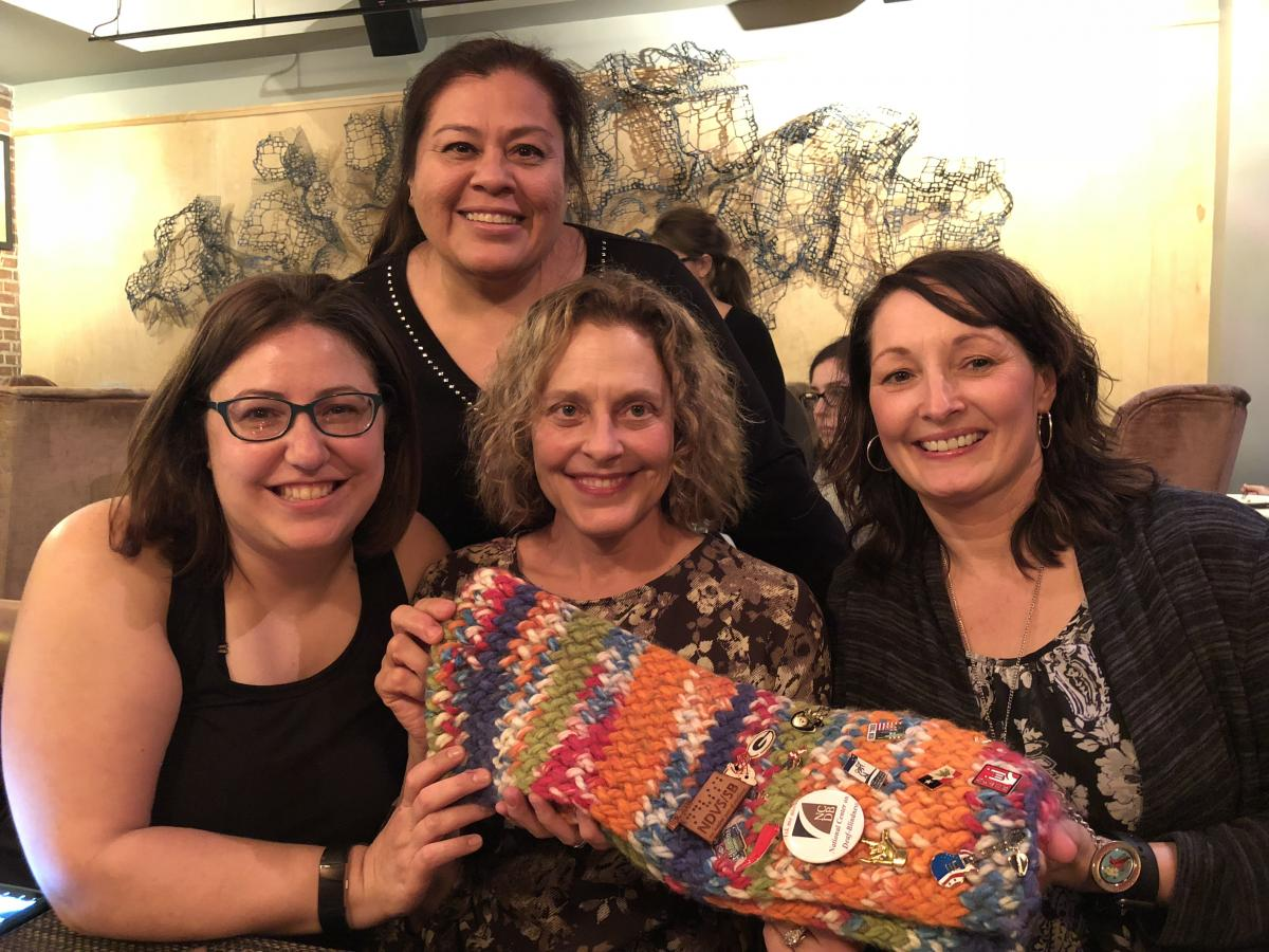 Four woman pose with FEC scarf at dinner.